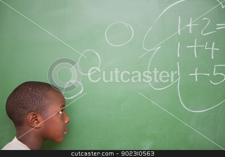 Smart schoolboy thinking about additions stock photo, Smart schoolboy thinking about additions in front of a blackboard by Wavebreak Media
