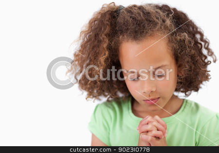 Cute girl praying stock photo, Cute girl praying against a white background by Wavebreak Media