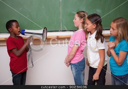 Schoolboy yelling through a megaphone to his classmates stock photo, Schoolboy yelling through a megaphone to his classmates in a classroom by Wavebreak Media