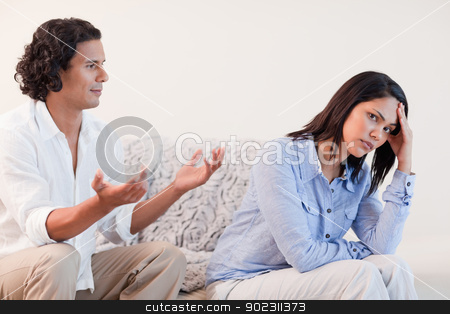 Man on the sofa trying to apologize to his girlfriend
