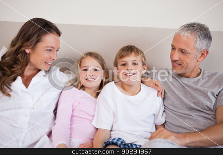 Good looking family lying on a bed