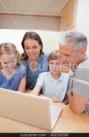 Portrait of a lovely family using a notebook stock photo, Portrait of a lovely family using a notebook in their kitchen by Wavebreak Media