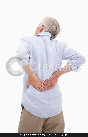 Portrait of a man having a back pain stock photo, Portrait of a man having a back pain against a white background by Wavebreak Media