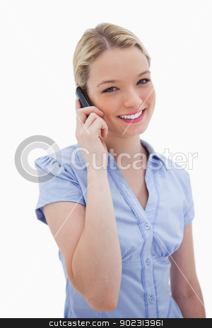 Smiling woman using cellphone stock photo, Smiling woman using cellphone against a white background by Wavebreak Media
