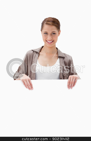 Smiling woman holding blank signboard stock photo, Smiling woman holding blank signboard against a white background by Wavebreak Media