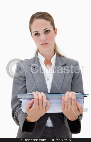Desperate office employee with pile of paperwork stock photo, Desperate office employee with pile of paperwork against a white background by Wavebreak Media