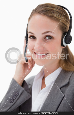 Side view of smiling female call center agent stock photo, Side view of smiling female call center agent against a white background by Wavebreak Media