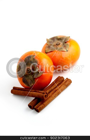 Persimmon Cinnamon stock photo, Closeup of persimmons and cinnamon on white background. by Henrik Lehnerer