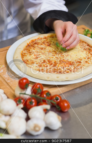 Pizza being garnished with basil leaf stock photo, Pizza being garnished with basil leaf on kitchen counter in restaurant by Wavebreak Media