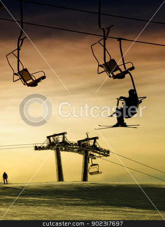 Skiing at sunset stock photo, Silhouette of a skier on the ski lift above ski slopes at sunset. by Sinisa Botas