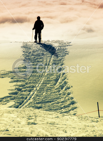 Snow trace stock photo, Silhouette of a skier who stands at the top of the hill. by Sinisa Botas