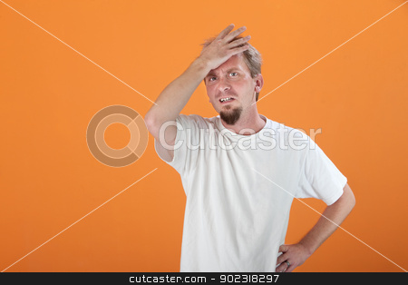 Tense Man stock photo, Tense Caucasian man with hand on his forehead on an orange background by Scott Griessel
