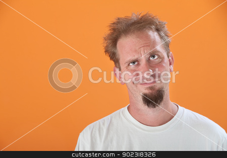 Messy and Annoyed Man stock photo, Annoyed Caucasian man looking up on an orange background by Scott Griessel