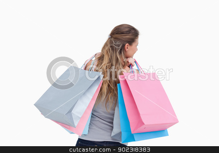 Back view of a woman holding shopping bags stock photo, Back view of a woman holding shopping bags against a white background by Wavebreak Media