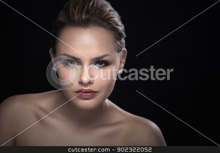 Portrait of a beautiful serious woman stock photo, Studio portrait of a beautiful serious intense young woman with bare shoulders looking directly at the camera against a dark background with copyspace by Instudio 68