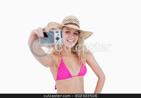 Beautiful teenage girl holding a camera while photographing hers stock photo, Beautiful teenager photographing herself with her camera against a white background by Wavebreak Media