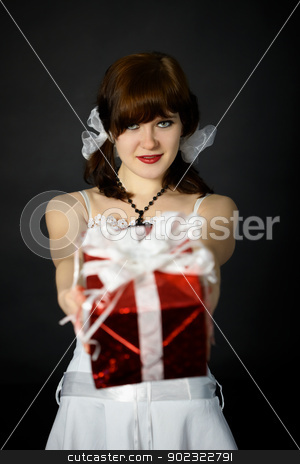 Young attractive woman gives a gift in red box stock photo, Young attractive woman gives us a gift in red box with a bow on dark background by Alexey Romanov