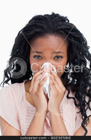 A young woman is blowing her nose in a tissue stock photo, A close up shot of a woman blowing her nose in a tissue by Wavebreak Media