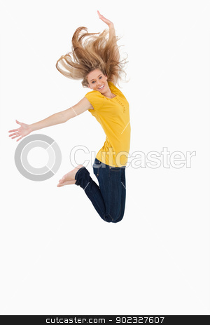 Blonde woman in yellow shirt jumping stock photo, Blonde woman in yellow shirt jumping against white background by Wavebreak Media