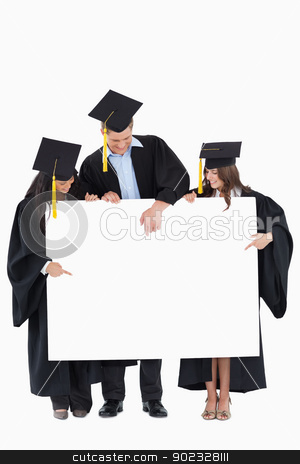 Three graduates pointing to the blank sign stock photo, Three graduates point to a spot on the balank sign which will be filled by infromation by Wavebreak Media