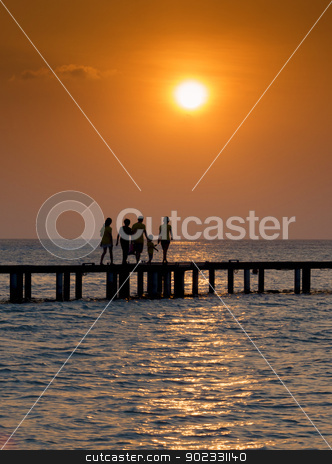 Family crossing bridge at sunset stock photo, Silhouette of family walking over a bridge at sunset by Christian Delbert