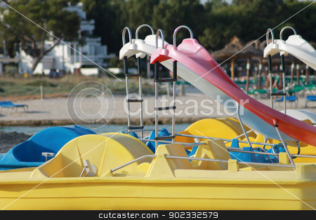 Slides on pedalo boats stock photo, Slides on pedalo boats with beach in background. by Martin Crowdy