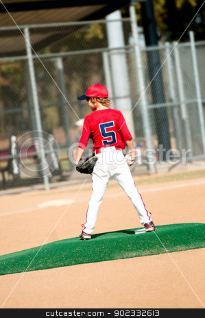 Young Boy Pitcher stock photo, Young boy in red jersey standing on pitching mound about to pitch. by Tammy Abrego