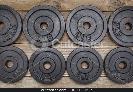 fitness weights stock photo, background of exercise weights -  iron dumbbell plates on a wooden deck by Marek Uliasz