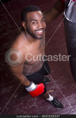Happy Boxer Pauses at Heavy Bag stock photo, A boxer pauses and looks up at the camera by Christopher Boswell