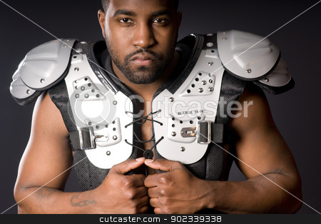 Football Player in Shoulder Pads stock photo, A male football player looks at the camera before taking off pads by Christopher Boswell