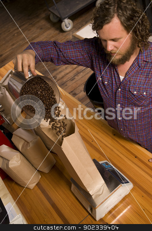 Coffee Packing Roaster Bags Beans stock photo, An experienced coffee roaster bags up his finished product. by Christopher Boswell