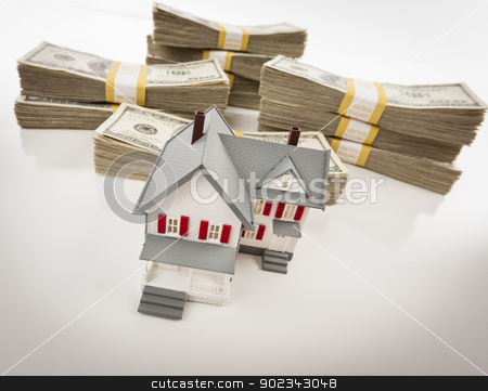 Stacks of Hundreds of Dollars with Small House stock photo, Stacks of One Hundred Dollar Bills with Small House. by Andy Dean
