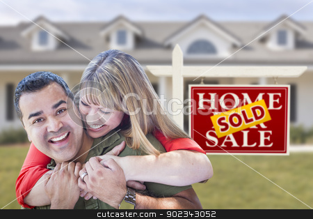 Mixed Race Couple in Front of Sold Real Estate Sign and House stock photo, Happy Mixed Race Couple in Front of Sold Real Estate Sign and New House. by Andy Dean
