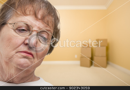 Sad Older Woman In Empty Room with Boxes stock photo, Sad Older Woman In Empty Room with Boxes - Concept for Foreclosure, Diviorce, Moving, etc. by Andy Dean