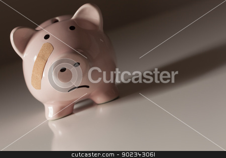 Piggy Bank with Bandage on Face stock photo, Piggy Bank with Bandage on Face on Dramatic Gradated Background. by Andy Dean