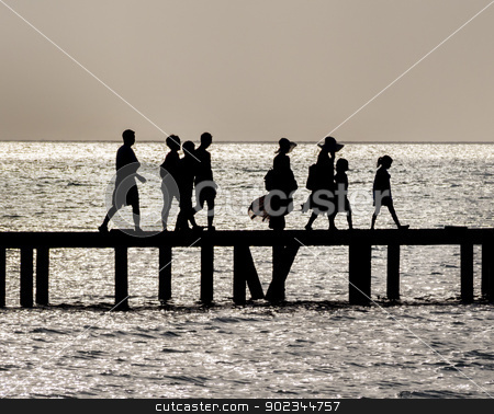 Family crossing bridge stock photo, Silhouette of Family crossing bridge by Christian Delbert