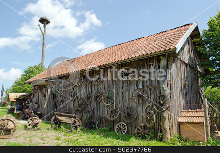 retro carriage wheel barn house bench stork nest  stock photo, retro carriage wheel hang on rural barn house. wooden benches. stork nest on top.  by sauletas