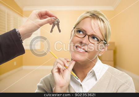 Woman Being Handed Keys in Empty Room with Boxes stock photo, Woman Holding Pencil Being Handed Keys in Empty Room with Boxes. by Andy Dean