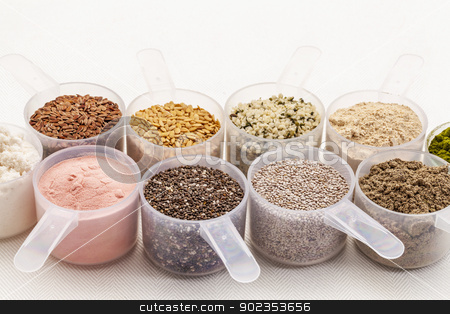 scoops of seeds and powders stock photo, scoops of superfood - healthy seeds and powders (white and black chia, flax, hemp, pomegranate fruit powder, wheatgrass,whey protein, maca root) on white tablecloth by Marek Uliasz