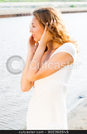 a young brunette caucasian girl at river stock photo, a young brunette european girl walking on river bank by Aikon