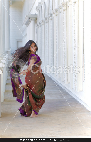 CareFree Indian Woman stock photo, A young, modern, 30 something, Indian woman with long black hair, dressed in a traditional sari runs barefoot down white hallway, looking over her shoulder and holding her shoes on a bright sunny day by Kim Wilson