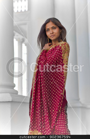 Indian Elegance stock photo, A young, 30 something, Indian woman with long black hair, dressed in traditional Indian attire (saree), stands near tall white columns for a dramatic and elegant portrait on a bright sunny day by Kim Wilson