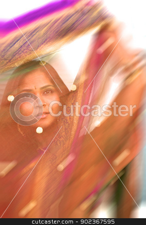 Colorful Blur of Indian Sari stock photo, A young, 30 something, Indian woman with long black hair, dressed in traditional Indian sari, is photographed through a purple colored shawl that is in movement, creating an artistic, creative blur by Kim Wilson
