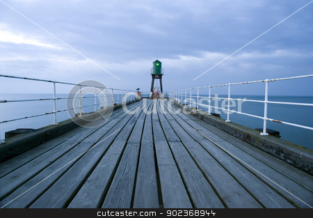 Navigation beacon on Whitby pier stock photo, View along the deserted wooden planking forming the promenade on top of the pier or breakwater at the harbour entrance in Whitby to the navigation beacon at the end by Stephen Gibson