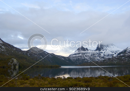 Cradle Mountain in winter stock photo, Cradle Mountain in Tasmania covered in winter snow reflected in the still water of the lake below by Stephen Gibson