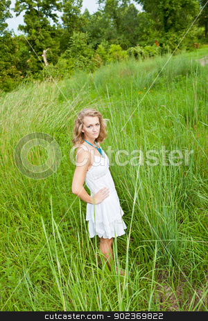 Woman in Tall Green Grass stock photo, Young woman in white summer dress, standing in a field of tall green grass. by Alex Antonuk