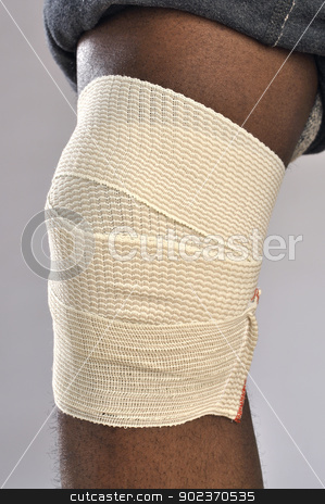 Knee injury stock photo, Closeup of injured knee with sport wrap on gray background by Chad Zuber