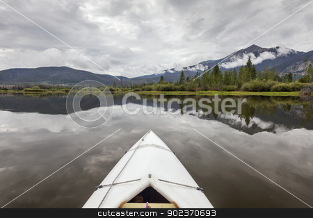 kayak on Lake Dillon stock photo, bow of a white kayak on Lake Dillon in Colorado Rocky Mountains, cloudy sky with water reflections by Marek Uliasz