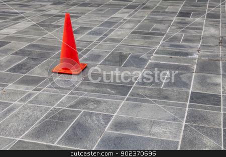 red traffic cone stock photo, red warning traffic cone on  a stone pavement by Marek Uliasz