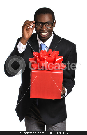 Gift for you stock photo, Young black nerdy businessman with glasses delivers gift with big red bow on white background by Chad Zuber